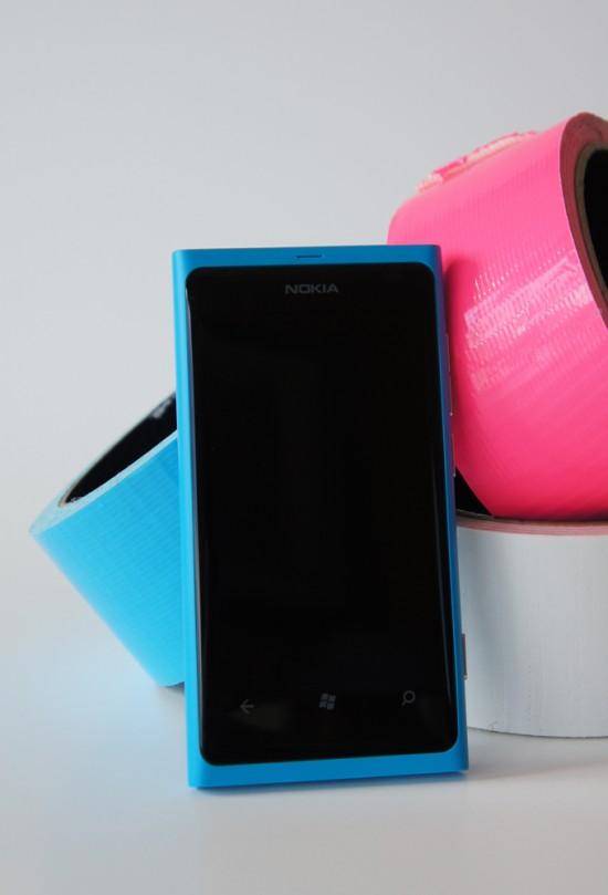 Sur la face avant, on retrouve les trois boutons capacitifs pour Windows Phone, soit, de gauche à droite, les boutons précédents, Windows et recherche - Le devant du Nokia Lumia 800, cyan