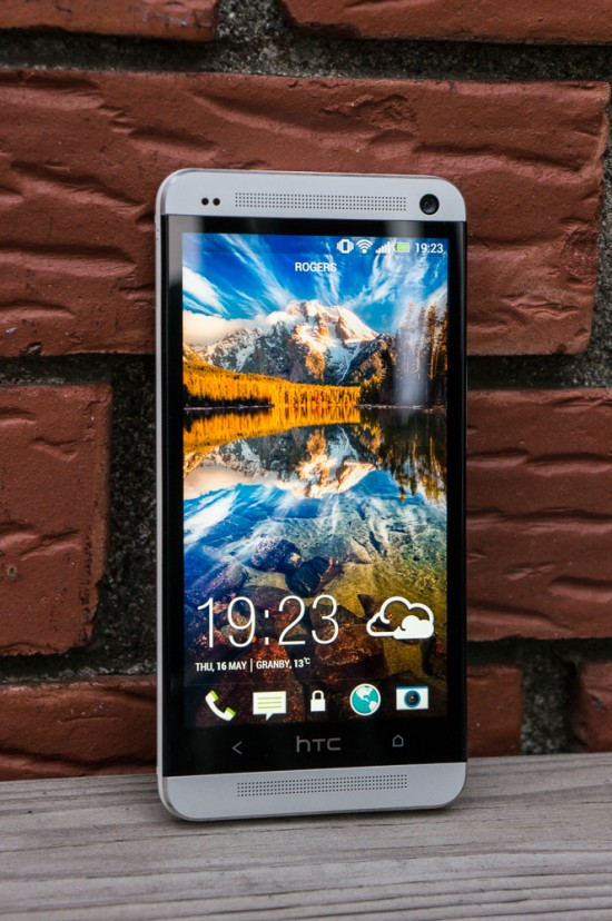 Le devant du HTC One est dominé par le généreux écran de 4,7 pouces. Aux couleurs vibrantes et aux angles de vision très large, il est facile à voir, même en plein soleil. Au-dessus et en-dessous de celui-ci se trouvent les hauts-parleurs HTC BoomSound. Sur le haut, on trouve également la caméra frontale ainsi que les usuels capteurs de proximité et de luminosité.