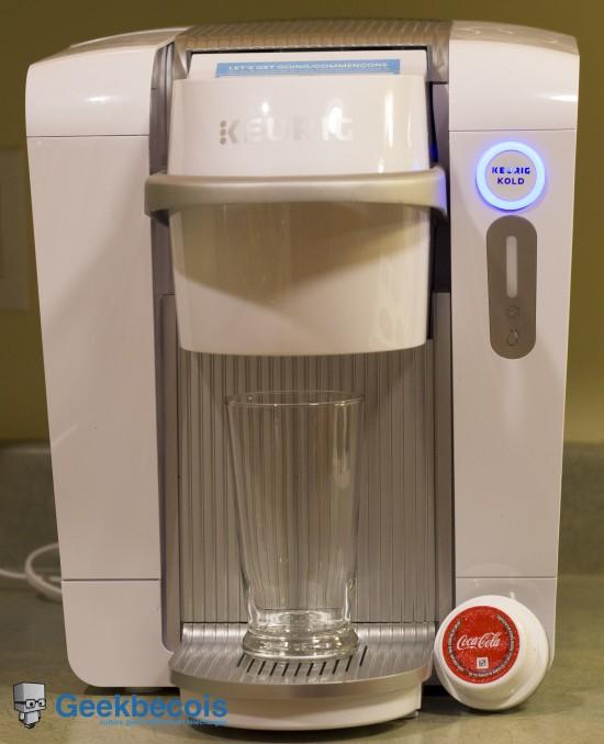 Système Keurig KOLD blanc vu de face avec un verre et une capsule Coca-Cola